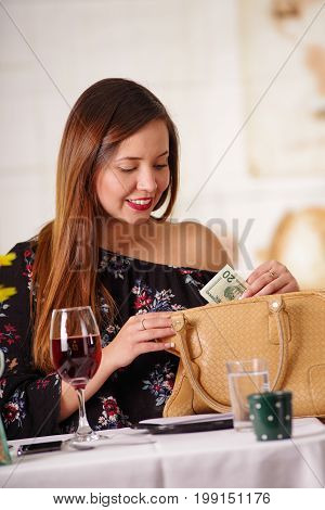 Portrait of beautiful woman taking money from her purse ready to pay the bill after the dinner, in a blurred background.