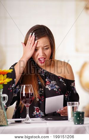 Portrait of shocked woman with a bill in her hand, after the dinner, in a blurred background.