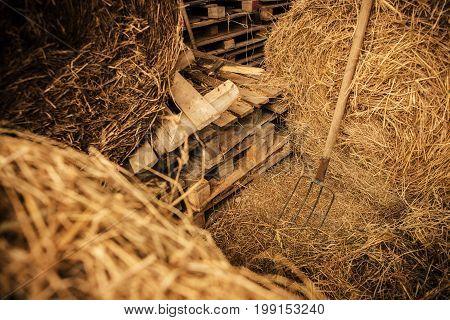 Hay Storage Barn Wood Pallets and Pitchfork Closeup Photo. Farm Barn Theme.
