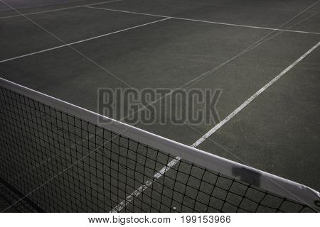 Tennis net on blue and green court at night