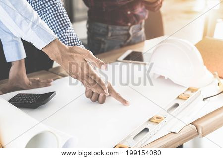 Image of engineer meeting for architectural project. working with partner and engineering tools on workplace. Engineer discussing architect concept.