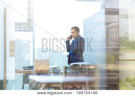 Businessman talking on a mobile phone while looking through modern corporate office window. Reflections of building interior in window glass.
