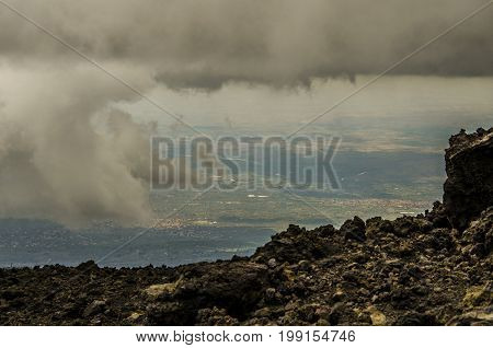 View of Sicilian territory between clouds from the top of Etna volcano