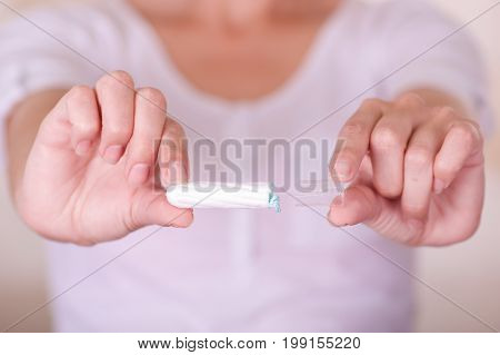 Close up of a young woman pointing in front of her a menstruation cotton tampon in a blurred background.
