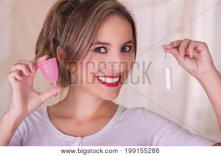 Close up of young beautiful smiling woman holding a menstruation cotton tampon in one hand and with her other hand a menstrual cup in a blurred background.