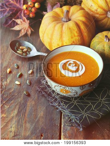 Autumn pumpkin soup with seeds on a wood table