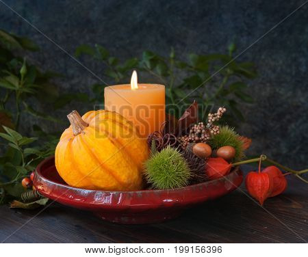 Autumn thanksgiving decor with candle and pumpkins