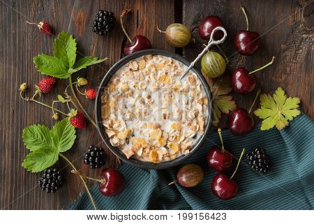 Healthy breakfast cereal with milk fresh Cherry Gooseberry Strawberry on a wooden background horizontal view from above