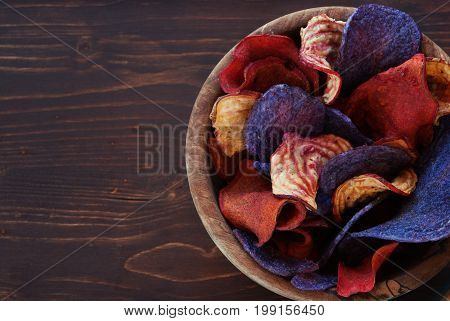 Colorful vegetable chips and beetroot chips served as a finger food snack in a wooden bowl