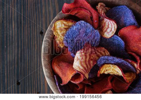 Crunchy organic dry potatoese chips and beetroot chips served as a finger food snack in a wooden bowl