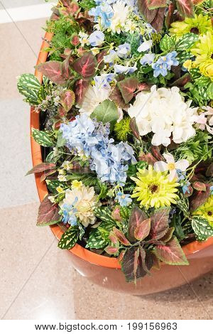 Closed up colorful artificial flowers in ceramic clay pot on marble stone floor for building decoration.