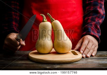 Chef holding knife and prepare for cutting butternut squash on wooden plate for cooking