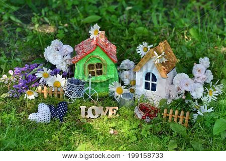 Two houses with decorations, love letters, flowers and berries. Miniature houses for greeting cards, wedding or birthday concept, real estate, downsizing, home ownership. Vintage summer background
