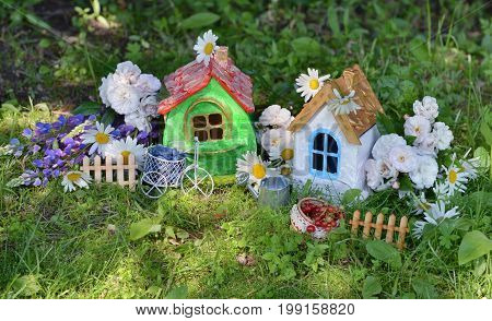 Two small houses with garden flowers and summer berries. Lovely miniature houses for greeting cards, wedding or birthday concept, real estate, downsizing, home ownership. Vintage summer background