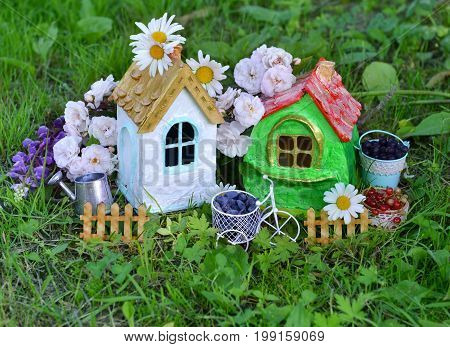 Two cute houses with summer berry, watering can and flowers in the garden. Lovely miniature houses for greeting cards, wedding or birthday concept, real estate, downsizing. Vintage summer background
