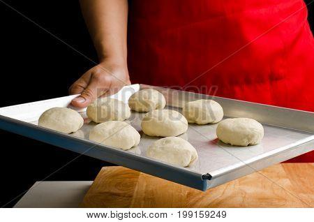 Buns dough ready to bake on baking tray,Homemade bakery cooking