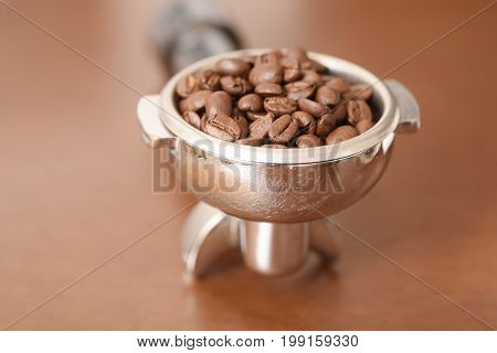 Roasted coffee bean in group head for making fresh coffee with coffee machine in the coffee shop