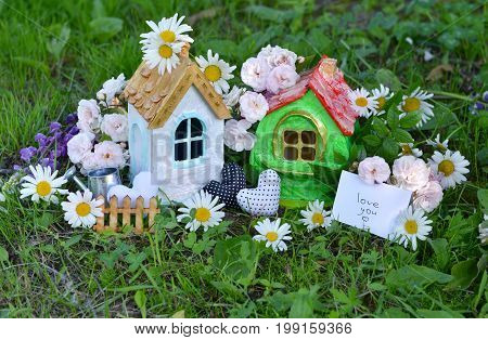 Toy houses with note and text love you, decorations, flowers in the grass. Lovely miniature houses for greeting cards, wedding or birthday concept, real estate, downsizing. Vintage summer background