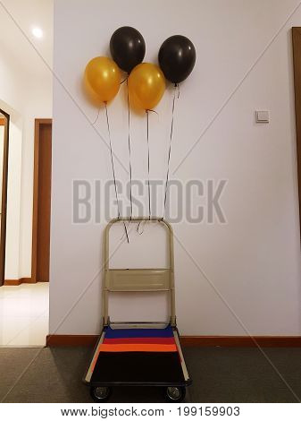 Smart, fun, creative and cost effective ideas to transport gifts with push trolley decorated with gold and black helium balloons laid with colourful papers