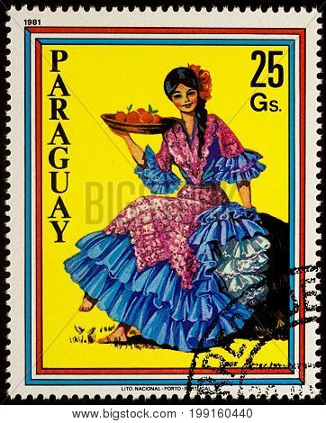 Moscow Russia - August 09 2017: A stamp printed in Paraguay shows beautiful young woman in Paraguayan traditional dress with fruits series