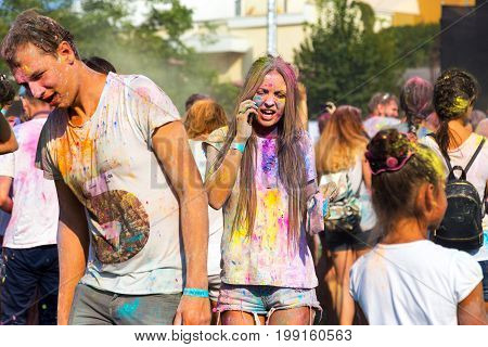 Odessa, Ukraine - August 5, 2017: Young Beautiful Girl Walking In Crowd Of People And Talking On The