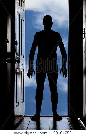 Naked man at doorway threshold in silhouette with blue cloudy sky background