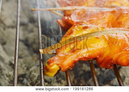 chicken leg grilled with smoke on iron stove