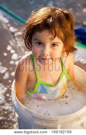 A young girl sits in a two gallon bucket full of soapy water in a driveway while her dad washes the car.