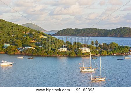 Tropical landscape of St Thomas Island near Coki Beach at sunrise US VI. Yachts and boats moored in the Caribbean Sea bay.