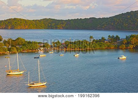 Tropical landscape in early morning of St Thomas Island in Caribbean Sea US VI. Yachts and boats bathing in the morning sun rays.