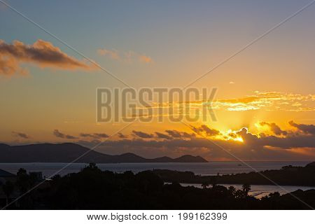 Sun about to appear above the clouds at sunset on St Thomas Island US VI. Poetic sunrise with a beach wave palms and fishing boat.