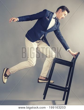 young handsoman businessman fooling aroung with chair, modern mem, lifestyle people concept
