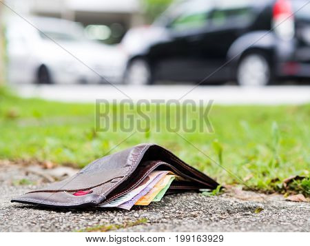 Lost leather wallet with money drop on sidewalk lost money concept copy space on top.