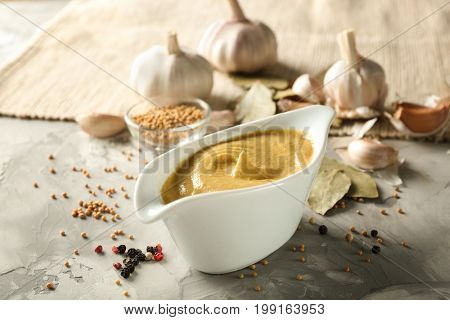 Composition with gravy boat of delicious mustard sauce on table