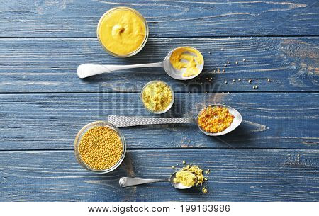 Mustard powder, seeds and sauces in dishes on wooden table