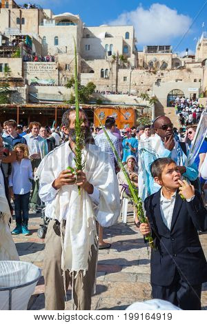 JERUSALEM, ISRAEL - OCTOBER 12, 2014:  The area in front of Western Wall of Temple filled with people. Morning autumn Sukkot, Blessing of the Kohanim. The Jews of ritual clothes - tallit