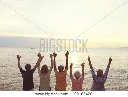 Senior group friends arm raised on the sunset beach