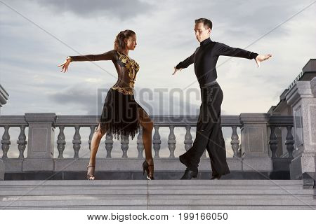 Pair of dancers dancing ballroom on sky background