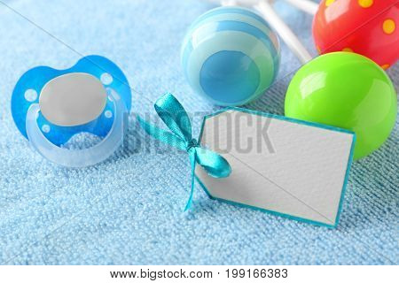 Greeting card with pacifier and rattle on towel