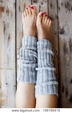 Woman's legs in knitted gray legwarmers closeup on wooden background.