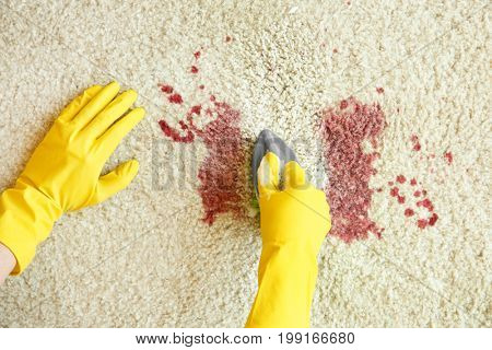Hands in rubber gloves cleaning carpet with brush and detergent