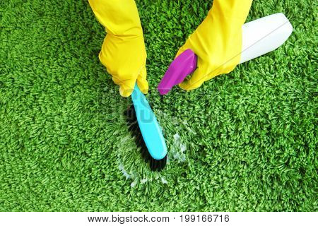 Hands of human in rubber gloves cleaning carpet with brush and detergent