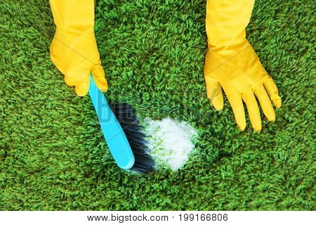 Hands in rubber gloves cleaning carpet with brush