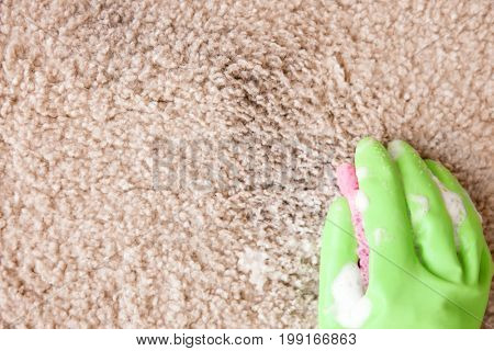 Hand in rubber glove cleaning carpet with sponge, close up