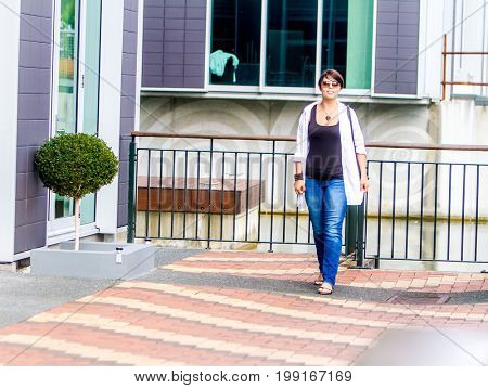 outdoor portrait of young happy lady on city background, casual lifestyle image