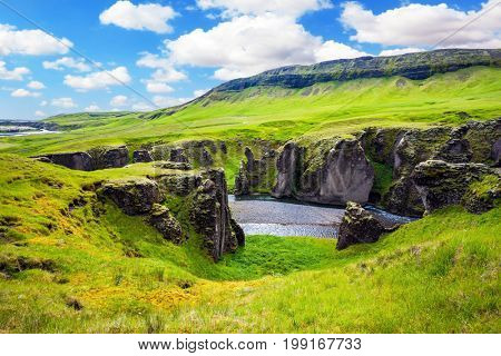 The striking canyon in Iceland. The Icelandic tundra in July. The concept of active northern tourism. Vertical huge rocks surround the stream with glacial water