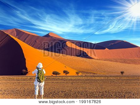 Elderly enthusiastic woman with a green backpack is taking pictures of a magnificent landscape. Orange, purple and yellow dunes of the Namib desert. The concept of extreme and exotic tourism