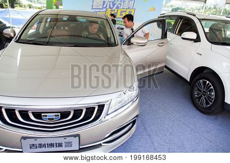 Dongguan, Guangdong, China - August 7, 2017: Car salesperson talking with prospective Geely brand Chinese automobile buyer at Dongguan car exhibition