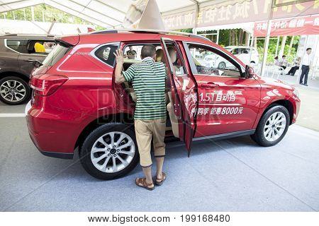 Dongguan, Guangdong, China - August 7, 2017: Prospective buyer inspecting a Haval brand Chinese automobile SUV on display at Dongguan car exhibition