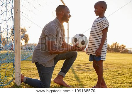 Father gives a ball to his son during a football game